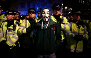 Protester wearing a Guy Fawkes mask stands infront of a line of riot police officers during a protest against budget cuts and energy prices in Westminster, central London